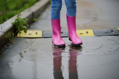 The child`s legs in gumboots walk on pools Royalty Free Stock Photography