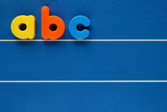 Child's letters. The letters a, b and c from a child's toy alphabet set, placed on a blue, lined background. Space for text elsewhere in the image Stock Photos