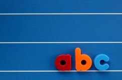 Child's letters. The letters a, b and c from a child's toy alphabet set, placed on a blue, lined background. Space for text elsewhere in the image Stock Images