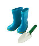 Child's little blue rubber gumboots with a shovel Stock Photo