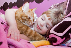 little girl sleeping with cat in bed Stock Photo