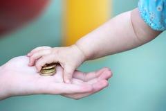 Child& x27; s mała ręka, bierze stos mały pieniądze od palmy Zdjęcie Stock