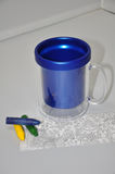 Child's mug with crayons. Blue plastic child's mug with crayons and drawing Royalty Free Stock Photos