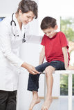 Child's neurologist testing knee reflex Royalty Free Stock Photo