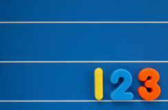 Child's numbers. The numbers 1, 2 and 3 from a child's toy alphabet set, placed on a blue, lined background. Space for text elsewhere in the image Stock Photo