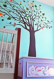 Child's nursery. Colorful nursery featuring crib, toy box, and wall mural of tree Stock Images