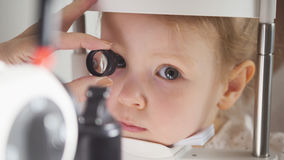 Child`s ophthalmology - doctor optometrist checks eyesight for little girl