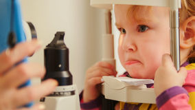 Child`s optometry - little girl checks eyesight in eye ophthalmological clinic - close up Royalty Free Stock Images