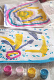 Child's paintings. Bright paintings by a child and paint pots Stock Photography