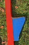 Child's Play. Old blue and red wooden stilt laying on grass Stock Photos