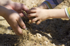Parenting. Adult and child hands playing with sand Royalty Free Stock Photos