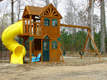 A child's play-set. Swing and slide outside on a cloudy winter day Royalty Free Stock Images