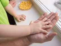 Child& x27; s ręka odpoczywa na palmie dorosła samiec, dziecko ochrona Zdjęcia Stock