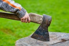 Child& x27; s ręka trzyma cioskę wtykał w drewnianej ołówkowej skrzynce zdjęcie stock