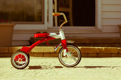 Child's rusted red tricycle standing ready. Child's rusted favorite cherished red tricycle standing ready and waiting for its owner to arrive on paving outside a Royalty Free Stock Image