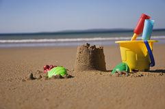 Child's sand bucket. And toys on scenic sunny beach with waves Stock Photo