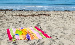 2 child`s sand pails and shovels on a striped beach towel at the ocean Stock Photos