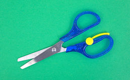 Child's scissors on green craft paper Royalty Free Stock Photo