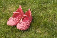 Child's shoes on garden grass. A little girl's shoes neatly placed on garden grass in summer Royalty Free Stock Image