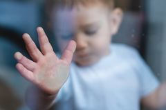 Child`s small hand is pressed against the window glass with reflection. Loneliness of children. Orphanage and orphans stock photos