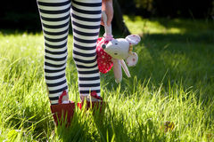 Child's stripy legs in a meadow. Child's legs in stripy tights and red boots standing in the long green grass of a meadow and holding a toy mouse for comfort royalty free stock photo