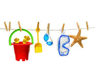 Child's summer toys on clothesline against white royalty free stock photography
