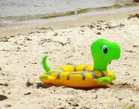 Child's swimming belt. Child's swimming turtle-formed belt on a sandy river bank Stock Images