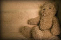 Child's teddy bear sitting on staircase