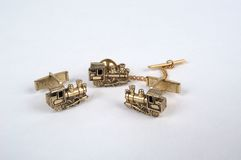 Child's tie tac and cufflink set. Antique child's cufflinks and tie tac in the shape of gold locomotives Stock Images