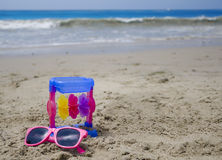 Child's toy and sunglasses on a beach Royalty Free Stock Photo
