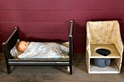 Antique child`s doll and potty chair. A child`s very old doll lies in a small wooden bed wrapped in a blanket with a nearby potty chair stock photography