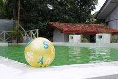 Child`s yellow ball floating in pool Royalty Free Stock Photos