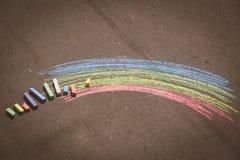 Child& x27; s-Zeichnung des Regenbogens und der Kreiden auf einer Straße Lizenzfreie Stockbilder