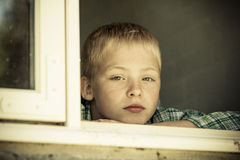 Child with sad expression looking out from window Royalty Free Stock Photography