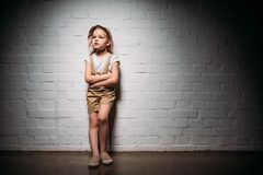 Child in safari costume with crossed arms standing. At white wall royalty free stock image