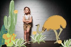 Child in safari costume with crossed arms standing at white wall with cactuses. And ostrich illustration royalty free stock photos