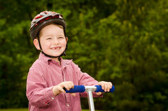 Child with safety helmet riding scooter. Outdoors Stock Image