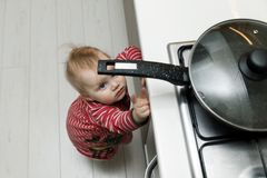 Child safety at home concept - toddler reaching for pan. On the stove in kitchen Royalty Free Stock Photos