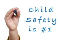 Child Safety Is Number 1. Child hand writing Child Safety Is #1 - isolated on white Stock Image