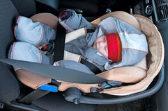 Child in safety seat. The child sleep in a safety seat on forward sitting of the car Royalty Free Stock Image
