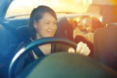 The child in a safety seat near to mother who sits on forward si. Tting of the car Stock Photography