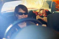 The child in a safety seat near to mother. The child in a safety seat near to mother who sits on forward sitting of the car Stock Photos