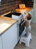 Child safety at the stove. A little baby child is curious and tries to take a hot pot on a stove Stock Photos