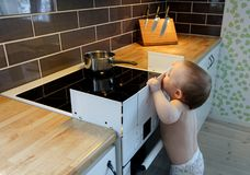 Child safety at the stove. Curious baby watch  a hot pan. Child safety at the stove. A little baby child is curious and watching a hot pot on a stove Stock Image