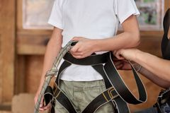 Child with safety straps. Closeup of child equipped with safety straps in adventure park Royalty Free Stock Photo