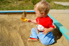 The child in a sandbox. The little boy sits in a sandbox, holds a scoop in a hand and throws up upwards sand Royalty Free Stock Photo