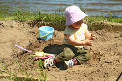 Child in sandbox. Little girl playing in a sandbox on a beach Royalty Free Stock Images