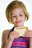 Child with a sandwich. A young girl eating a peanut butter and jelly sandwich Royalty Free Stock Photography