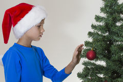Child in Santa cap start to decorate Christmas tree Stock Photography