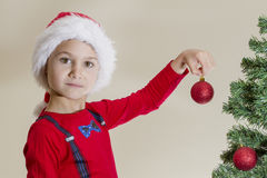 Child in Santa cap with Xmas toy while decorating Christmas tree Royalty Free Stock Image